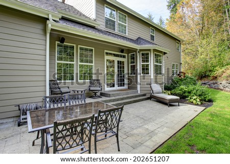 Large classic house with patio area and green lawn. - stock photo