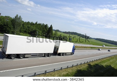 large clean white truck driving into distance, shot from behind and from above - stock photo