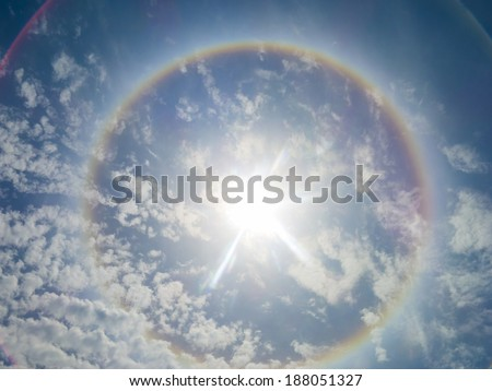 Large colorful rainbow Ring around the sun caused by high altitude Ice Crystals s - stock photo