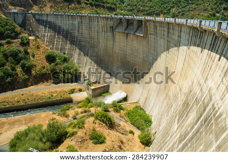 Large concrete reservoir dam  surrounded by forest - stock photo
