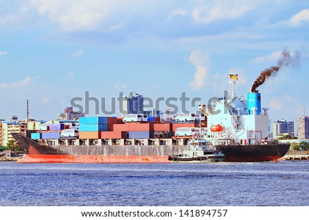 Large container cargo ship and support tug boat  - stock photo