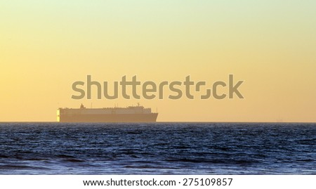 Large container freighter on the horizon during sunset. - stock photo