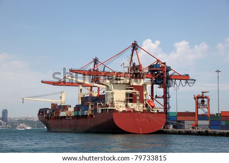 Large container ship in a dock at industrial port (logos and brandnames removed) - stock photo