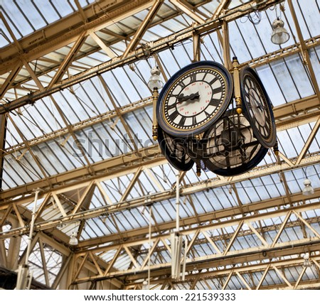 Large decorative clock hanging from a train station roof  - stock photo