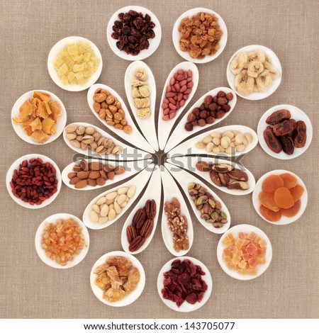 Large dried fruit and nut selection in white porcelain bowls over hessian background. - stock photo
