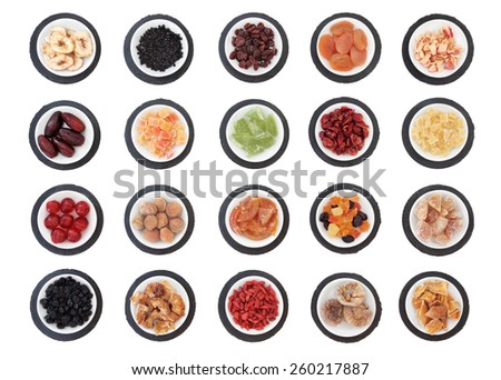 Large dried fruit selection in white bowls on slate rounds over white background. - stock photo