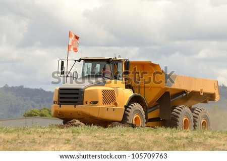 Large dump tractor moving dirt and rocks for a airport runway extension project in Oregon - stock photo