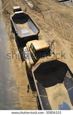 Large dump trucks are ready for big loads on construction job site - stock photo