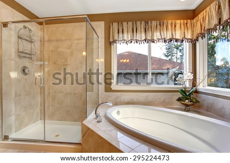 Large elegant master bathroom with shower, and big bath tub. - stock photo