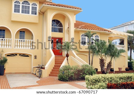 Large, elegant three story home in Tropical Florida with lush tropical landscape seated on a waterfront canal.  Dual stairs lead to the two door grand entryway of the mansion. - stock photo