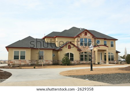Large expensive modern house yellow stucco and stone - stock photo