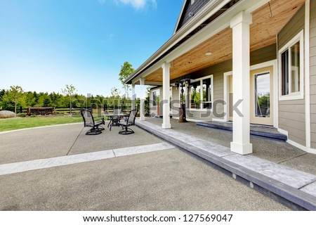 Large farm country house with long covered porch and terrace. - stock photo