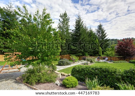 Large fenced backyard with patio and play set. Large green lawn and garden - stock photo
