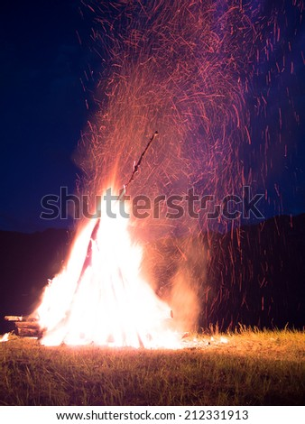 Large fire with sparks lit in the middle of the field at night - stock photo
