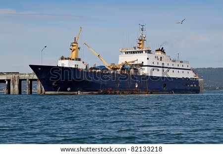 Large fish processing boat in the deep water dock in Homer, Alaska on a sunny summer day - stock photo