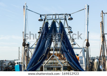 Large fishing boat in Coffs Harbour with blue netting fishing nets hanging to dry from back of the ship - stock photo