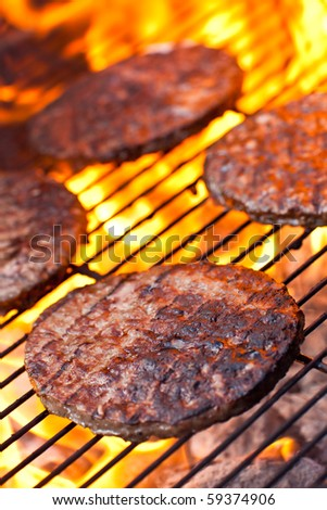Large flame grilled beefburgers on a BBQ - stock photo