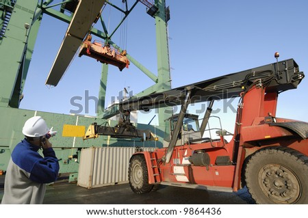 large forklift truck lifting containers in port, port-worker in hard-hat supervising on the phone - stock photo