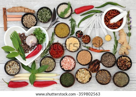 Large fresh and dried herb and spice sampler with wooden bowls and china heart shaped dish with mortar and pestle over distressed white wooden background. - stock photo