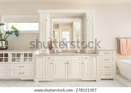Large furnished bathroom in luxury home with tile floor, fancy cabinets, large mirror, and bathtub - stock photo