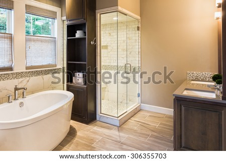 Large furnished bathroom in luxury home with tile floor, fancy cabinets, large mirror, shower, and bathtub - stock photo