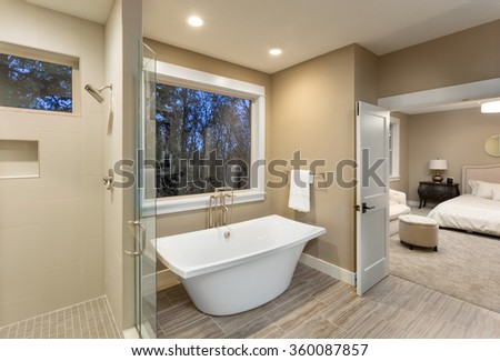 Large furnished bathroom in luxury home with tile floor, shower, bathtub, and view of master bedroom - stock photo