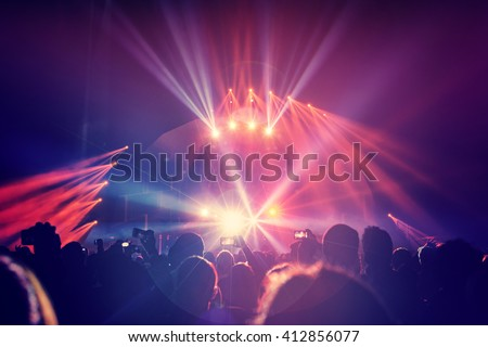 Large group of a happy young people enjoying concert, having fun spending time in a night club, dancing in bright laser beams, men partying, celebrating holidays - stock photo