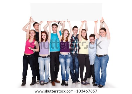 Large group of cheerful people holding a banner over heads - stock photo