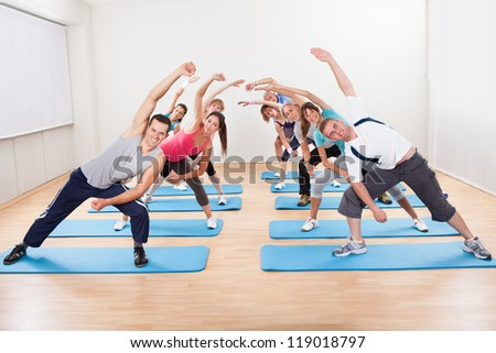 Large group of diverse people doing aerobics exercises in a gym standing on blue mats - stock photo