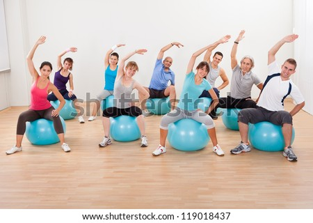 Large group of diverse people in a pilates class exercising in a gym practicing balance and control - stock photo
