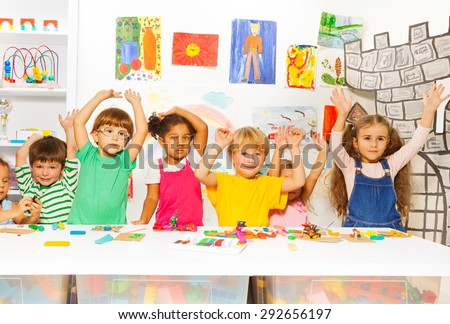 Large group of happy diverse looking preschool boys and girls play with modeling clay in class in kindergarten - stock photo