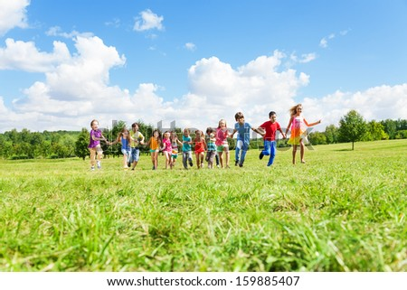 Large group of happy smiling kids, boys and girls running in the park on sunny summer day in casual clothes - stock photo