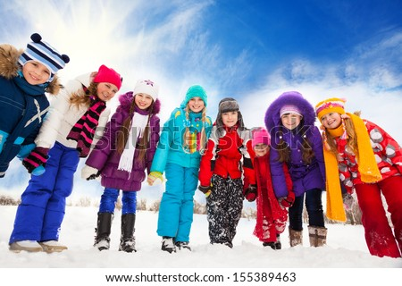 Large group of kids, boys and girls 5-10 years old bending down, holding hands, standing together in a row - stock photo