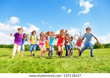 Large group of kids, friends boys and girls running in the park on sunny summer day in casual clothes - stock photo