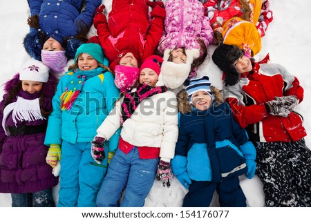 Large group of kids laying in snow together in one big lump, view from above - stock photo