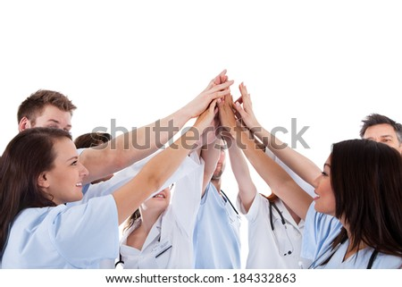 Large group of motivated doctors and nurses standing in a circle giving a high fives gesture with their hands meeting in the centre  conceptual of teamwork isolated on white - stock photo