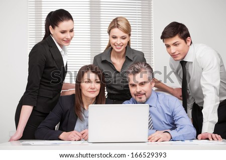 Large group of people looking together at laptop. Smiling and searching something, discussing ideas  - stock photo