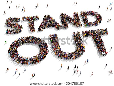 "Large group of people seen from above gathered in the shape of the text ""STAND OUT"" - stock photo"