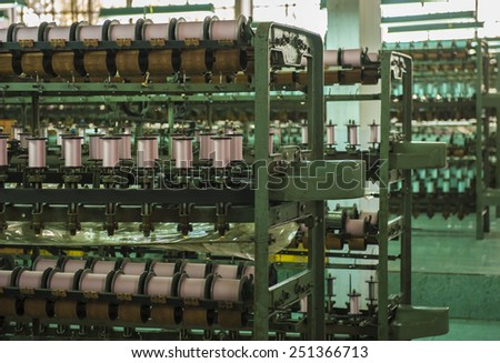 large group of rolling bobbin thread cones on a warping machine in a textile mill. - stock photo