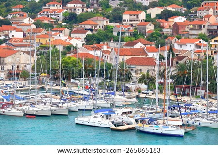 Large group of sail boats tied to the pier in front of an old town, Trogir, Croatia - stock photo