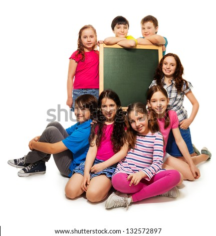 large group of school kids, boys and girls sitting by the blackboard, isolated on white - stock photo