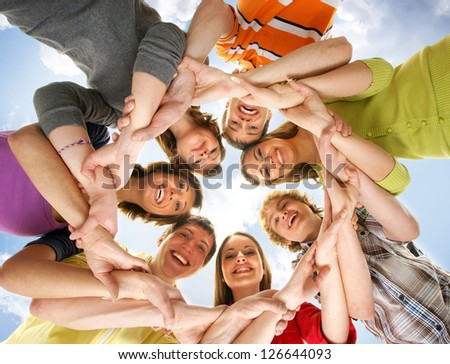 Large group of smiling friends staying together and looking at camera isolated on blue background - stock photo
