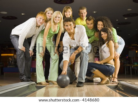 Large group of teenagers standing and smiling in bowling alley. One person is holding ball and playing. Looking at camera - stock photo