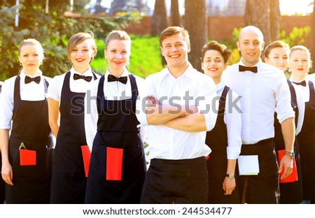 Large group of waiters and waitresses standing in row. - stock photo