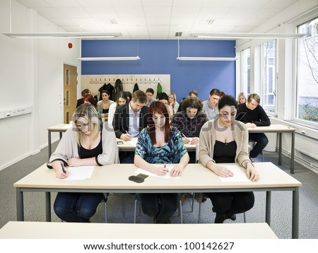 Large group of young adult students in the classroom - stock photo