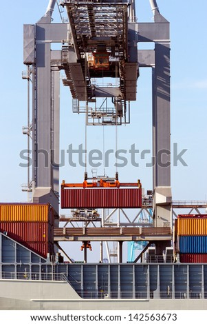 Large harbor crane lifting a sea container - stock photo