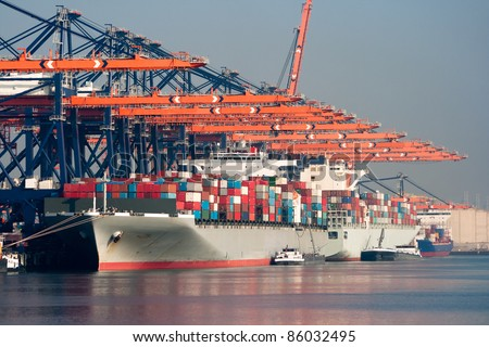 Large harbor cranes loading container ships in the port of Rotterdam. - stock photo