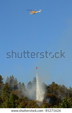 Large helicopter with a 500 gallon water bucket working a natural cover fire near Roseburg Oregon - stock photo