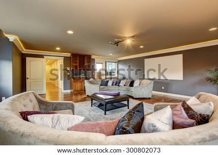 Large home theater room with projection unit and gray sofas. - stock photo