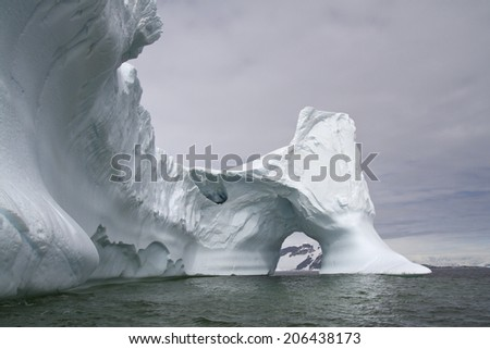 large iceberg with a through arch in Antarctic waters - stock photo